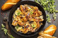 Grilled chicken wings with lemon and herbs. Grilled chicken wings with lemon and greens on a dark background Royalty Free Stock Photo