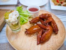 Grilled chicken wings with tomato sauce on the table in restaurant.Thai food style. stock image