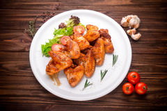 Grilled chicken wings with vegatables and seasoning on a wooden Royalty Free Stock Photo
