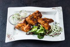 Grilled chicken wings on a white plate. With onions and herbs stock photo