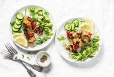 Grilled chili honey lime chicken skewers with rice and avocado salsa on light background, top view. Flat lay stock images