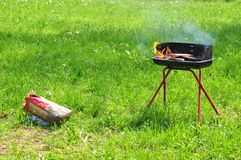 Grilled with coal bag. Grill on a green grass field,near a bag of coal Royalty Free Stock Image