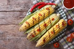 Grilled corn with chili and tomato sauce top view Royalty Free Stock Photos