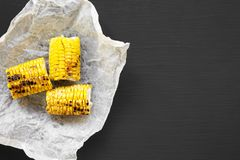 Grilled corn on the cob ove black background, top view. Summer food. From above, flat lay. Copy space royalty free stock photos