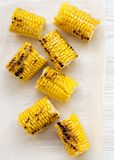 Grilled corn on the cob over white wooden surface, top view. Summer food. From above, overhead, flat lay. Close-up.  royalty free stock image