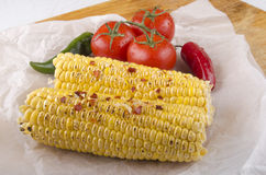 Grilled corn on the cob and tomato Stock Photography
