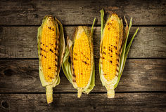 Grilled corn cobs on vintage wood background Stock Photo