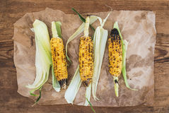 Grilled corn over oily craft paper and rustic wooden background, top view. Stock Image