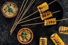 Grilled corn pierced with sticks. Top view of grilled corn pierced with sticks and bowls of sauce Royalty Free Stock Image
