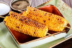 Grilled Corn with salt and butter on plate on dark wooden background, Closeup. Ingredients on table royalty free stock photos