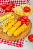 Grilled corn. With tomatoes on the wooden plate Stock Photography