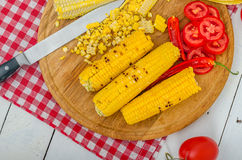 Grilled corn. With tomatoes on the wooden plate Royalty Free Stock Photo