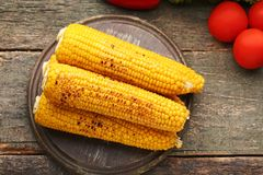 Grilled corns. Tasty grilled corns on grey wooden table Stock Images