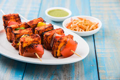 Grilled cottage cheese or also known as Paneer Tikka Kebab or chili paneer or chilli paneer or tandoori paneer in india India, bar. Becued in red sauce Royalty Free Stock Image