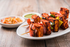 Grilled cottage cheese or also known as Paneer Tikka Kebab or chili paneer or chilli paneer or tandoori paneer in india India, bar. Becued in red sauce Stock Photography