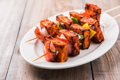 Grilled cottage cheese or also known as Paneer Tikka Kebab or chili paneer or chilli paneer or tandoori paneer in india India, bar. Becued in red sauce stock photo