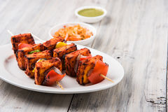Grilled cottage cheese or also known as Paneer Tikka Kebab or chili paneer or chilli paneer or tandoori paneer in india India, bar. Becued in red sauce Royalty Free Stock Photos