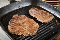 Grilled cube steaks. In a cast iron grill stock photography