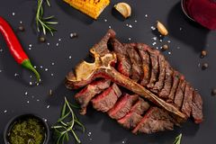 Grilled cut meat on rustic black background. Fried steak on bone, restaurant serving with spices and herbs, top view stock photography