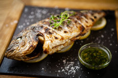 Grilled dorada fish with lemon and spinach Royalty Free Stock Photography
