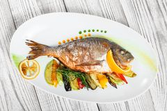 Grilled dorado fish with baked vegetables and rosemary on plate on wooden background close up. Healthy food. Top view royalty free stock photo
