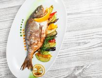 Grilled dorado fish with baked vegetables and rosemary on plate on wooden background close up. stock image