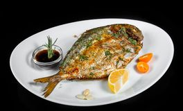 Grilled dorado fish with greens and lemon on black background isolated. Healthy food. Top view royalty free stock photos