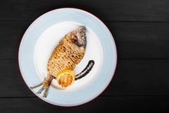 Grilled dorado fish with lemon and truffle sauce on plate on wooden background. Delicious dish of seafood. Top view stock photos