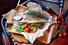Grilled Dorado fish on a wooden board. Over vintage background Stock Photography