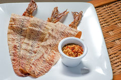 Grilled dried squid. With sweet and sour sauce on wooden background Stock Photography