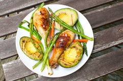 Grilled drumsticks chicken, avocado, onion and asparagus Stock Photos