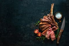 Grilled dry aged tomahawk steak sliced as close-up. On dark background royalty free stock photos