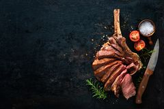 Grilled dry aged tomahawk steak sliced as close-up. On dark background royalty free stock photo