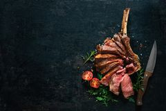 Grilled dry aged tomahawk steak sliced as close-up. On dark background stock images