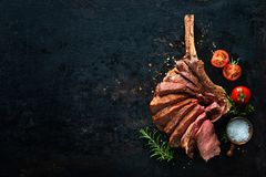Grilled dry aged tomahawk steak sliced as close-up. On dark background stock photos