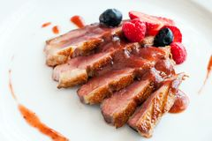 Grilled duck breast with sweet red fruit dressing. Stock Photography