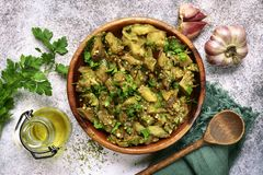 Grilled eggplant salad with parsley, garlic and olive oil.Top vi. Grilled eggplant salad with parsley, garlic and olive oil in a wooden bowl over light slate stock photos