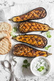 Grilled eggplant and sauce tzatziki on a light background, top view. Stock Photos