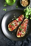Grilled eggplant stuffed with tomatoes, nuts, pomegranate and yo. Gurt dressing on a dark plate over black slate, stone or concrete background.Top view Stock Photo