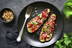 Grilled eggplant stuffed with tomatoes, nuts, pomegranate and yo. Gurt dressing on a dark plate over black slate, stone or concrete background.Top view Royalty Free Stock Photography