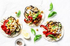 Grilled eggplant, sweet peppers, cauliflower and spicy chickpeas vegetarian tortillas on a light background, top view. Healthy foo. D concept royalty free stock images