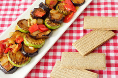 Grilled eggplant and zucchini with peppers and onions. Steamed vegetables in square  plate on a checkered tablecloth.crispbread Royalty Free Stock Photo