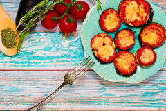 Grilled eggplants with cheese and herbs. Ready to eat dish - grilled sliced eggplants with cheese, tomatoes, herbs and spices. Raw ingredients lie nearby on Royalty Free Stock Photos