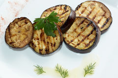 Grilled eggplants decorated with green leaf. Top view. White plate Royalty Free Stock Photography