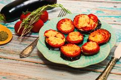 Grilled eggplants with tomatoes and cheese. Dinner recipe idea - eggplants grilled with tomatoes, cheese and herbs. Plate with dish stands on wooden table in Stock Photography