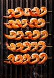 Grilled a fait frire des crevettes roses sur des brochettes sur le gril Photographie stock