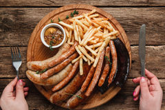 Grilled fat sausages with french fries, flat lay Royalty Free Stock Image