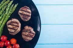 Grilled filet mignon with asparagus and tomatoes. Beef sreak on rustic background stock images