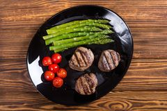 Grilled filet mignon with asparagus and tomatoes. Beef sreak on rustic background royalty free stock photo