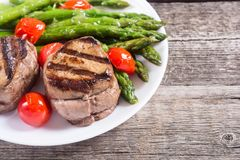 Grilled filet mignon with asparagus and tomatoes. Beef sreak on rustic background royalty free stock image